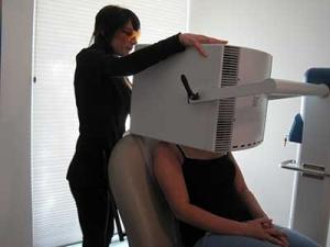 Esthetician Anne Marie Johnson realiza un tratamiento de terapia de luz azul en un paciente.